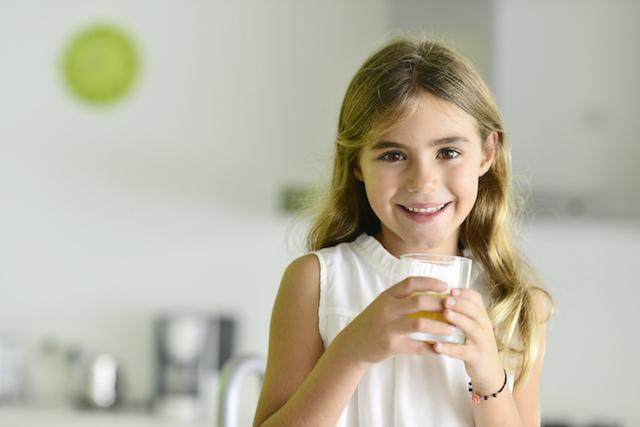 Young girl holding glass of water | Dentist in White Bear Lake MN