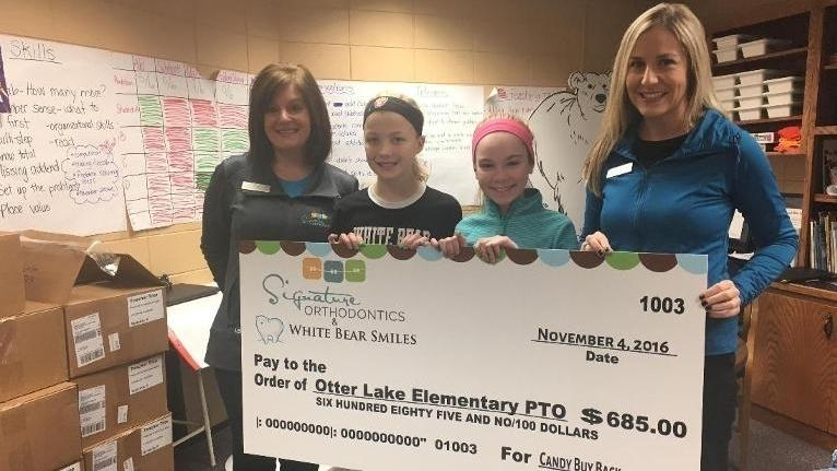 White Bear Smiles staff holding donation to elementary school | Dentist in White Bear Lake MN
